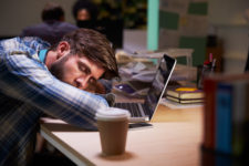 Male Office Worker Asleep At Desk Working Late On Laptop